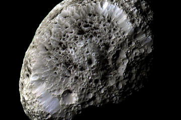 The subject of this image bears a remarkable resemblance to a porous sea sponge, floating in the inky black surroundings of the deep sea.  Indeed, the cold, hostile and lonely environment of deep water is not too far removed from deep space, the actual setting for this image in which one of Saturn's outer moons, Hyperion, can be seen in incredible detail. This image was taken by Cassini when the spacecraft performed a flyby of the small moon on 26 September 2005.  During the flyby, Cassini got more than it bargained for as Hyperion unleashed a burst of charged particles towards the spacecraft, effectively delivering a giant 200-volt electric shock. It appears that Hyperion's surface becomes electrostatically charged as it is bathed in charged particles – both those constantly streaming out into space from the Sun and those trapped within the magnetic field of the moon's host planet, Saturn.  While astronomers expected many bodies throughout the Solar System to be charged, the data from the Cassini flyby represent the first-ever experience of a charged natural object in space other than our own Moon.  Hyperion is shaped a bit like a potato and, with dimensions of 410 x 260 x 220 km, is one of the largest bodies in the Solar System known to be so irregular. Its odd, almost 'bubbly' appearance, can be attributed to it having a very low density for its size. Because of these properties the entire moon is porous, like a sponge, with well-preserved craters of all shapes and sizes packed together across its surface. Scientists think that this moon is mostly made up of water ice, with small amounts of rock.  Images taken using infrared, green and ultraviolet filters were combined to create this view. The natural redness of Hyperion's surface was toned down in this false-colour image to enhance the visibility of the moon's surface features  Cassini was approximately 62 000 km from Hyperion when the image was taken, and the image scale is 362 m per pixel.