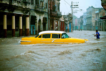 People and vehicles wade through a flooded street during an intense rainstorm in Havana, on April 29.