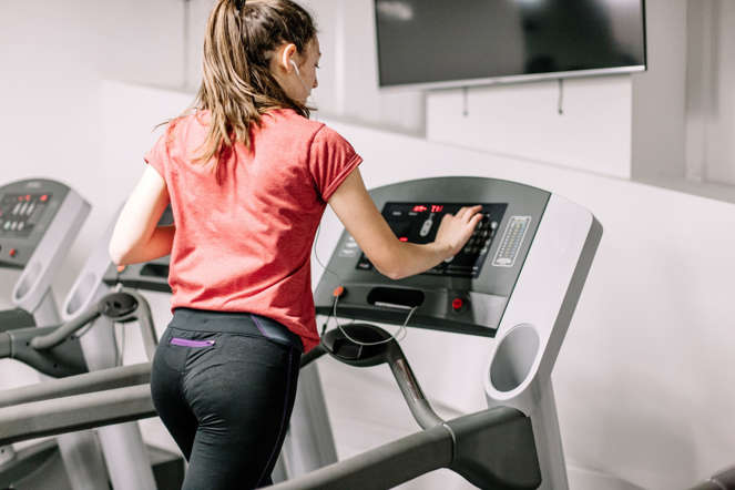 Young female operating a treadmill, wearing earphones