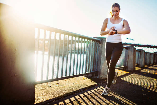 A young athletic woman goes for a morning run, running along the paths at Tom McCall Waterfront Park in Portland, Oregon.  She checks her smart watch, which acts as a pedometer, stopwatch, and heart rate monitor.  The sun shines from behind the Burnside bridge, giving a warm glow to the image.  Horizontal with copy space.
