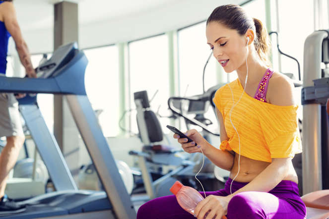 Young female holding smart phone and listening music in the gym.