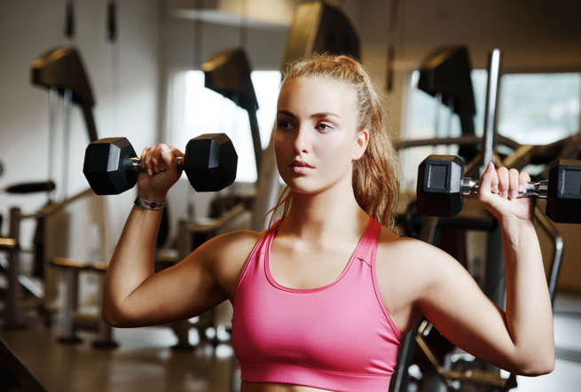 Beautiful woman wearing a pink top exercsing with dumbbells in a gym