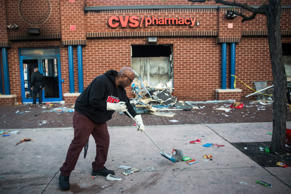 Jerald Miller helps clean up debris from a CVS pharmacy that was set on fire during rioting after the funeral of Freddie Gray, on April 28, 2015 in Baltimore.