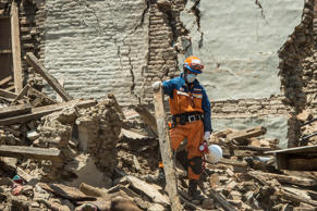 A member of the Japanese disaster relief team looks on among debris from a collapsed building on May 2, 2015 in Sankhu, Nepal.