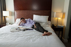 Man in hotel watching tv in bed. Tooga/Getty Images