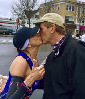In this April 20 photo provided by Paige Tatge, her mother, Barbara Tatge, left, kisses an unknown spectator in Wellesley, Mass., as she ran in the Boston Marathon. It's a tradition for male runners to kiss the women attending Wellesley College as they line the marathon route. Barbara made good on a dare by her daughter, Paige, that she kiss a man as she ran along the route.