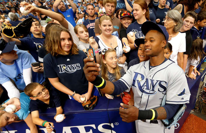 The Tampa Bay Rays' Tim Beckham uses a fan's phone to take a selfie with him before the game against the Baltimore Orioles on May 3 in St. Petersburg, Fla.