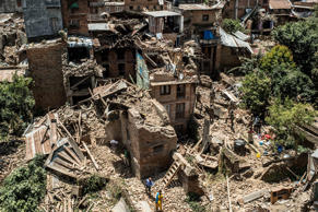 File: People move between collapsed buildings on May 2, 2015 in Sankhu, Nepal.