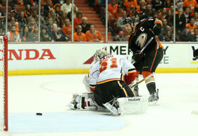 Ryan Getzlaf #15 of the Anaheim Ducks gets the puck through goalie Karri Ramo #31 of the Calgary Flames but it goes just wide of the net.
