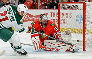 Goalie Corey Crawford of the Chicago Blackhawks stops the shot by Kyle Brodziak #21 of the Minnesota Wild in game two of their playoff series May 3 in Chicago. The Blackhawks won 4-1 to take a 2-0 series lead.