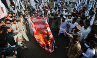 Supporters of the Jamaat-ud-Dawa Islamic organization burn the U.S. flag during an anti-American rally in Karachi April 6, 2012.