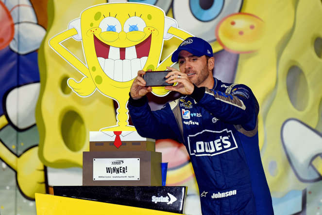 Jimmie Johnson, driver of the #48 Lowe's Chevrolet, takes a selfie with the trophy in Victory Lane after winning the NASCAR Sprint Cup Series SpongeBob SquarePants 400 at Kansas Speedway on May 9, 2015, in Kansas City, Kansas.
