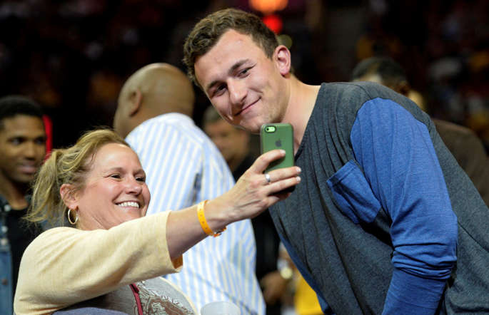 Cleveland Browns quarterback Johnny Manziel poses for a photograph with a fan during game five of the second round of the NBA Playoffs on May 12 in Cleveland.