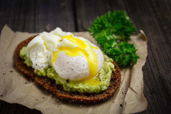 Healthy, clean eating: rye toast with avocado and poached egg top view