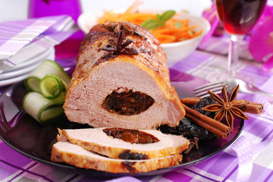 roasted pork loin stuffed with prune and spices on festive table