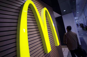 FILE - In this Dec. 17, 2014 file photo, a man walks by a McDonald's logo in front of its restaurant in Tokyo. McDonald's is set to unveil its latest plans to revive its sputtering business on Monday, May 4, 2015. (AP Photo/Eugene Hoshiko, File)