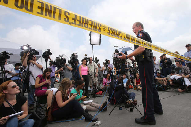 Waco Police Sgt. Patrick Swanton addresses the media as law enforcement continues to investigate the motorcycle gang related shooting at the Twin Peaks restaurant, Monday, May 18, 2015, in Waco, Texas, where nine were killed Sunday and over a dozen injured. About 170 gang members charged with engaging in organized crime are each being held on a $1 million bond and authorities say charges of capital murder are expected in the wake of the Central Texas shooting.
