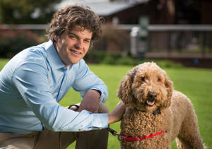 "A file picture of Dr. Brian Hare kneeling with a dog for promotion of a show ""Is Your Dog a Genius?"""