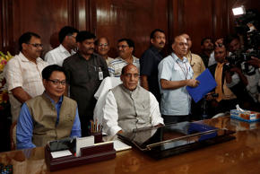 File: India's new Home Minister Rajnath Singh (C) sits inside his office after taking charge of his office inside the home ministry in New Delhi May 29, 2014. On the left is Minister of State for Home Affairs Kiren Rijiju.