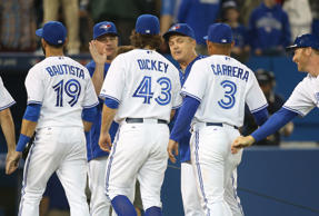 R.A. Dickey #43 of the Toronto Blue Jays is congratulated on his win by manager John Gibbons #5 during MLB game action against the New York Yankees.