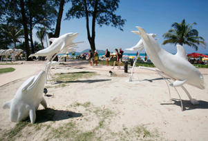 Tourists walks past dolphin sculptures at Patong beach in Phuket.