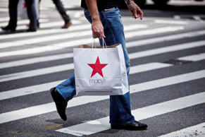 A shopper carries a Macy's Inc. bag while crossing the street in New York on Friday, May 10, 2013.