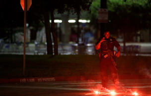 An armed police officer stands guard at a parking lot near the Curtis Culwell Center where a provocative contest for cartoon depictions of the Prophet Muhammad was held Sunday, May 3, 2015, in Garland, Texas.