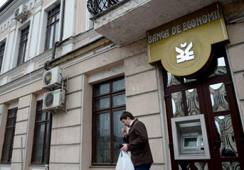 A man leaves an ATM of Banca de Economii in Chisinau, Moldova, on March 27, 2015.