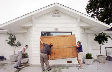 File photo of workers boarding up a restaurant in Pensacola, Fla., in preparation for an approaching hurricane.