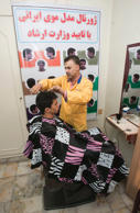File: Ali Abedi, hairstyle instructor and designer, cuts hair as he and his model pose for the media at Isar (Devotion) hairdressing institute in Tehran July 12, 2010, in front of a poster of Iranian haircuts approved by the Ministry of Guidance.