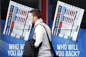 A member of the public walks past a betting shop window with a display for the General Election in Govan, Scotland, Wednesday, May 6, 2015. Britain goes to the polls in a General Election Thursday.