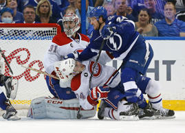 Ryan Callahan #24 of the Tampa Bay Lightning crashes into Alexei Emelin #74 of the Montreal Canadiens in front of Carey Price #31.