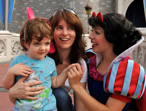 File picture of Tina Fey (center) and daughter Alice as they pose with Disney character Snow White.