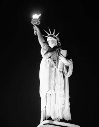 The torch of the Statue of Liberty blazes in the night as the lights are turned on once again at the island in New York Harbor, May 8, 1945, V-E Day, on which the official announcement of the unconditional surrender of Germany was proclaimed. Two service men stand guard at the base of the statue.