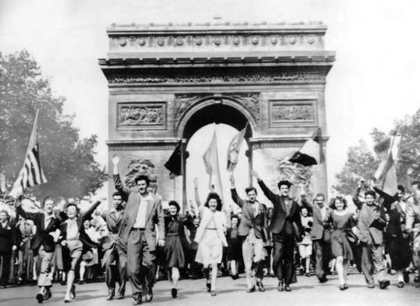 Parisians march through the Arc de Triomphe jubilantly waving flags of the Allied Nations as they celebrate the end of World War II on May 8, 1945.  German military leaders signed an unconditional surrender in Reims, France, on May 7.