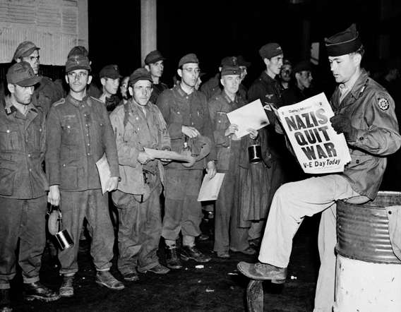 Pfc. Clarence K. Ayers of Evansville, Ind., reads the news of V-E Day as newly arrived German prisoners stand on a New York City pier, May 8, 1945.
