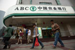 Pedestrians walk past a branch of the Agricultural Bank of China Ltd. in Beijing, China