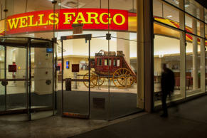 A pedestrian walks past a Wells Fargo & Co. bank branch at night in New York...