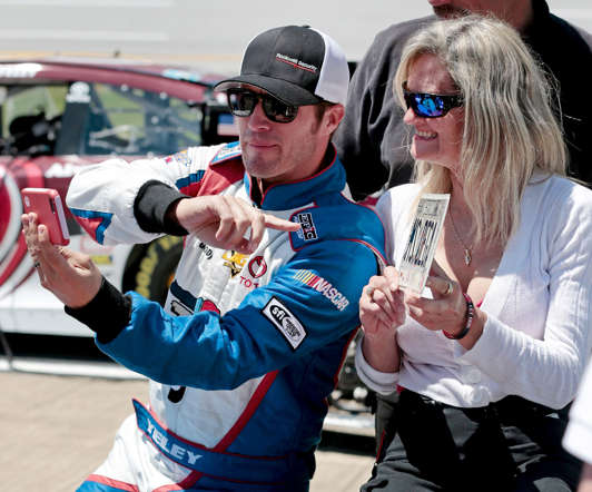 NASCAR driver J.J. Yeley takes a selfie with a race fan during qualifying for a Sprint Cup Series auto race at Talladega Superspeedway on May 2, 2015, in Talladega, Ala.