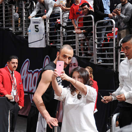 Manu Ginobili of the San Antonio Spurs poses for a selfie with a fan before a playoff game against the Los Angeles Clippers on April 22, 2015, at the Staples Center in Los Angeles.