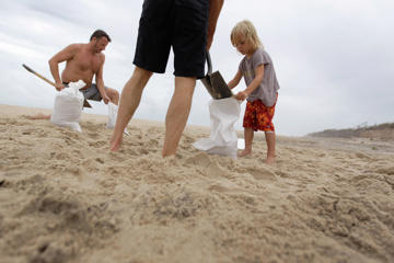 (From left) Marc Murphy, John Wellmann and 4-year-old Callen Murphy fill sandbags on the beach as they prepare their home for Hurricane Irene on August 27, 2011 in Water Mill, New York.