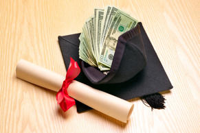 Rolled diploma and mortar board with US banknotes.