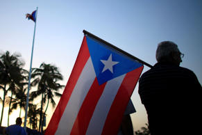 People gather in front of the Puerto Rico's Capitol building to protest against Gov. Alejandro Garcia Padilla's budget proposal for the next fiscal year in San Juan, Thursday, April 30, 2015. Legislators struck down a key part of a plan to overhaul the island's tax system early Thursday, raising concerns about the U.S. territory's economic future and its ability to pay off a heavy public debt.