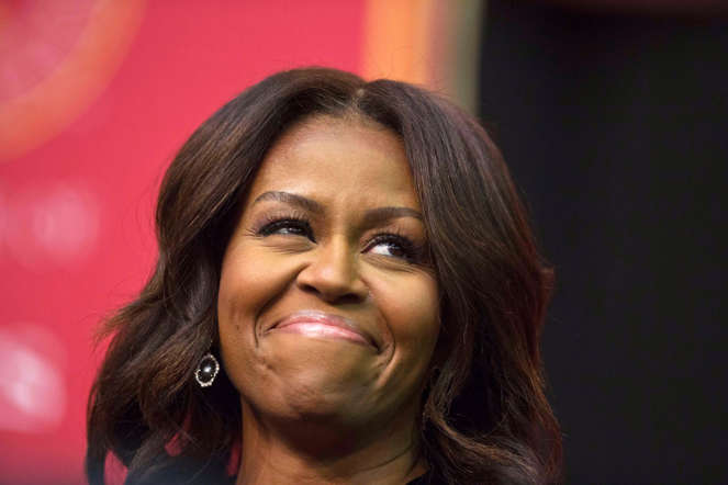 First lady Michelle Obama smiles towards the crowd before she speaks during the Tuskegee University's spring commencement, Saturday, May 9, 2015, in Tuskegee, Ala. (AP Photo/Brynn Anderson)