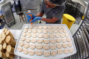 In a Wednesday, April 29, 2015 file photo, Norma Rutter, of Bulger, Pa., puts smiley faces on a sheet of cookies, at an Eat'n Park in Robinson Township, Pa.