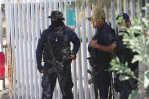 Mexican state police stand guard near the entrance of Rancho del Sol, near Vista Hermosa, Mexico. Refugio Ruiz/AP