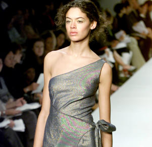 A model wears a shimmering asymmetrical wrap dress in a fashion show in New York.