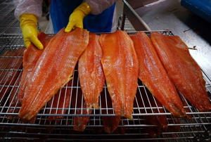 A worker inspects a Tasmanian salmon fillet at the processing plant in Dover, south of Hobart. Grilled Tasmanian salmon with nuts is a specialty here.