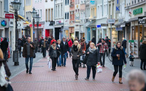 Shoppers pass retail stores on a pedestrianized shopping street in Bonn, Germany.