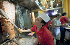 Doner chef Cango from Turkey cuts doner kebab in a Turkish restaurant in Berlin, Germany.